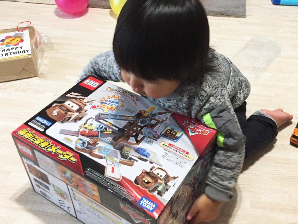 早く開けて欲しくて箱を抱える息子