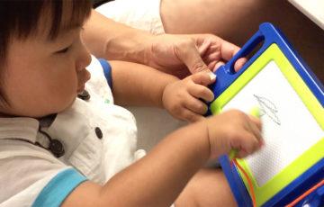 新幹線でお絵描きボードに夢中の息子